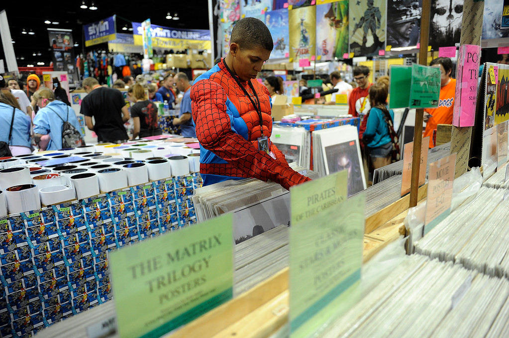 . Ronnie Jefferson, 33, dressed as Spiderman, flips through a stack of posters during Denver Comic Con at the Colorado Convention Center in Denver, Colorado on June 14, 2014. (Photo by Seth McConnell/The Denver Post)