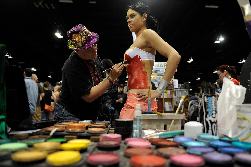 . Mythica von Griffyn uses body paint to make up Ruta Banyte, 23, as Wonder Woman during Denver Comic Con at the Colorado Convention Center in Denver, Colorado on June 14, 2014. (Photo by Seth McConnell/The Denver Post)