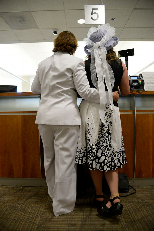 . Fran Simon (L) and Anna Simon stand at the counter to get their license at the Denver County clerk\'s office where they began issuing same sex marriage licenses July 10, 2014.  (Photo by John Leyba/The Denver Post)