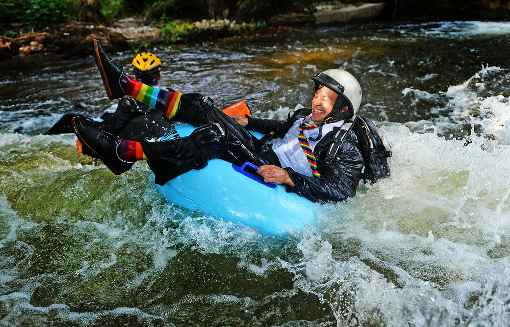 . Jeff Kagan, right, is the founder of the seventh annual Boulder\'s Tube to Work Day, July 15, 2014. Around 40 participants took their tubes down Boulder Creek on their way to work. The event typically takes place in June to line up with Boulder\'s Bike to Work Day, but safety concerns on the creek forced it to be pushed back into July this year. (Photo by RJ Sangosti/The Denver Post)