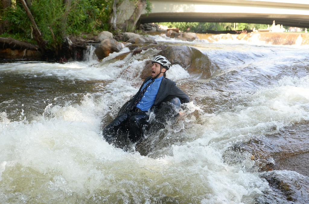 . Quayle Hodek, dressed in a suit and tie, floats down Boulder Creek during Boulder\'s Tube to Work Day, July 15, 2014. Around 40 participants took their tubes down Boulder Creek on their way to work. (Photo by RJ Sangosti/The Denver Post)