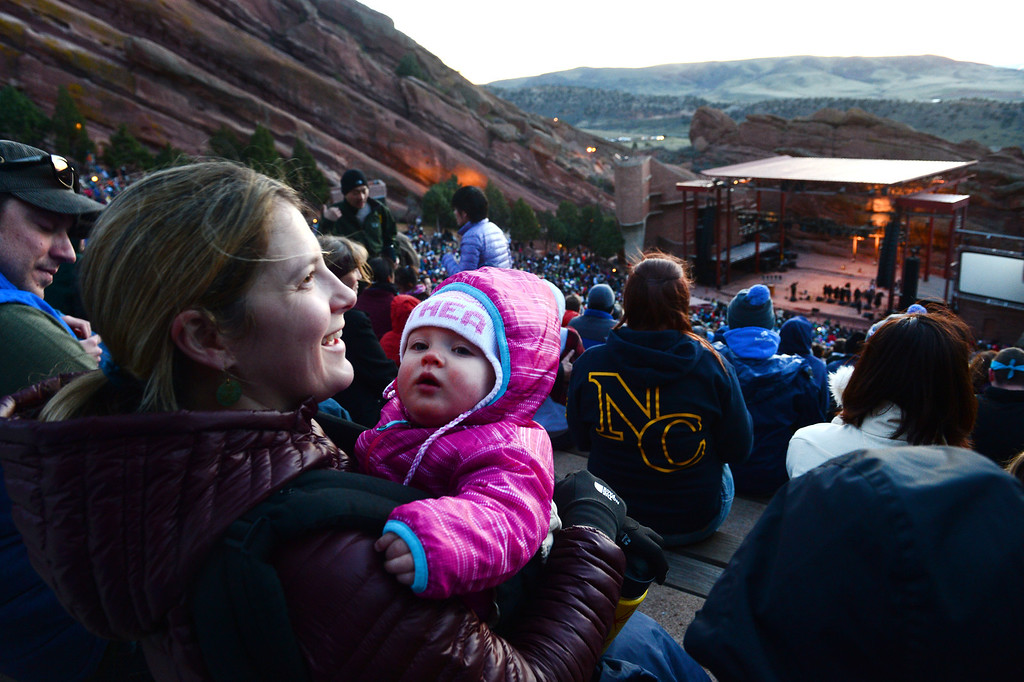 ". Jana Lomax holds her 10 month old daughter Althea while they and her husband Spencer, left, enjoy  the 67th annual Easter sunrise service  at Red Rocks Amphitheater in Morrison, Colorado, on April 17, 2014.  Superintendent Patrick L. Demmer gave the sermon which was entitled ""What are you looking for?\"".  The popular annual event, which hosts thousands of worshipers, is sponsored by the Colorado Council of Churches.  (Photo By Helen H. Richardson/ The Denver Post)"