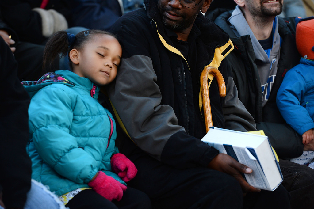". Destiny Taylor, 5, left, sleeps on the shoulder of her father Pastor D.P. Taylor, middle, as they, listen to the exuberant and passionate sermon given by superintendent Patrick L. Demmer during the 67th annual Easter sunrise service  at Red Rocks Amphitheater in Morrison, Colorado, on April 17, 2014.  Demmer\'s sermon was entitled ""What are you looking for?\"".  The popular annual event, which hosts thousands of worshipers, is sponsored by the Colorado Council of Churches.  (Photo By Helen H. Richardson/ The Denver Post)"