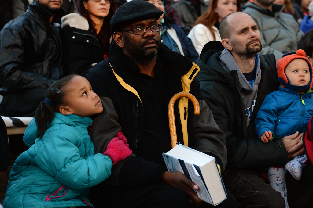 ". Destiny Taylor, 5, left, snuggles next to her  father Pastor D.P. Taylor, middle as they, listen to the  exuberant and passionate sermon given by superintendent Patrick L. Demmer during the 67th annual Easter sunrise service  at Red Rocks Amphitheater in Morrison, Colorado, on April 17, 2014.  Demmer\'s sermon was entitled ""What are you looking for?\"".  The popular annual event, which hosts thousands of worshipers, is sponsored by the Colorado Council of Churches.  (Photo By Helen H. Richardson/ The Denver Post)"