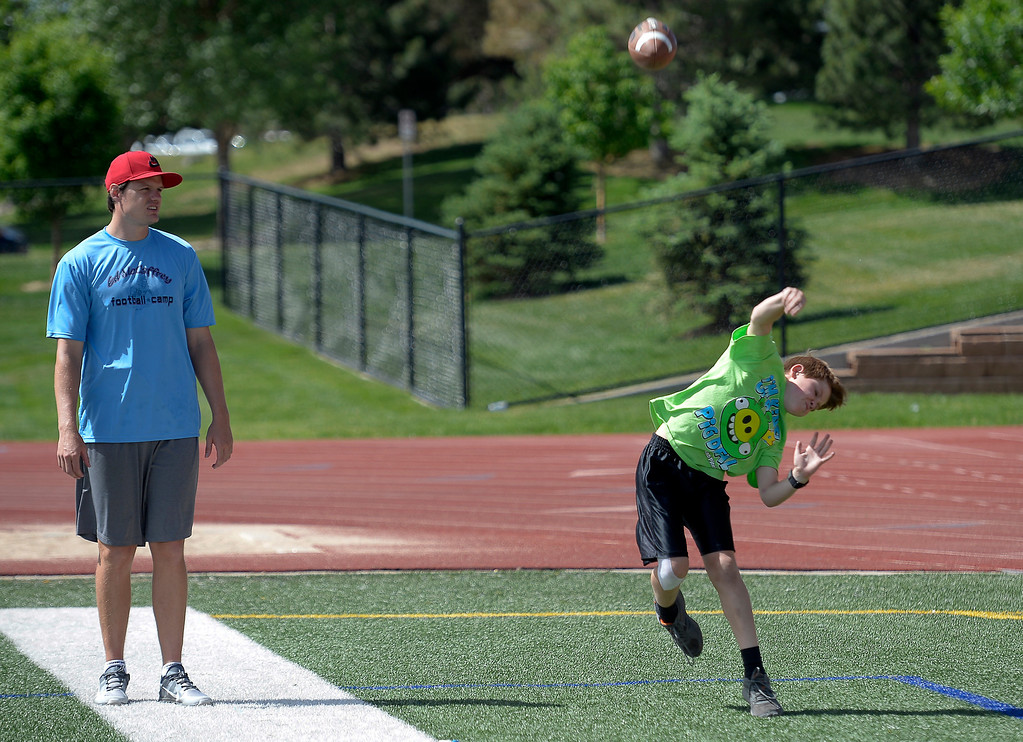 ". Miami Dolphins quarterback Aaron Corp helps out the quarterbacks during The Ed McCaffrey ""Open\"" Football Camp June 25, 2013 at Valor High School. Former Broncos star receiver Ed McCaffrey and other former pro football players conduct a football camp for kids ages 8-15 at Valor Christian High School.  (Photo By John Leyba/The Denver Post)"