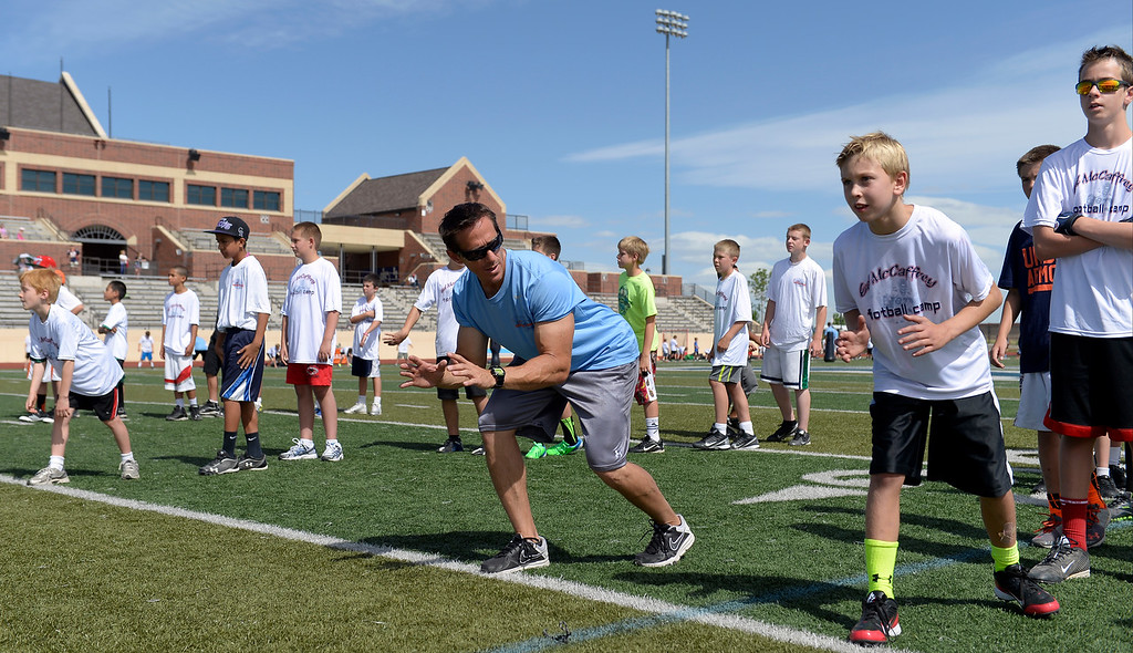". Trainer Loren Landow helps out during The Ed McCaffrey ""Open\"" Football Camp June 25, 2013 at Valor High School. Former Broncos star receiver Ed McCaffrey and other former pro football players conduct a football camp for kids ages 8-15 at Valor Christian High School. (Photo By John Leyba/The Denver Post)"