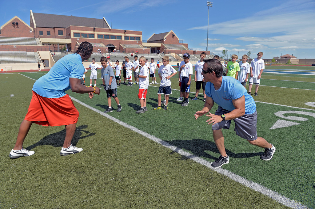 ". Loren Landow (R) helps out coach Jesse Jones during  The Ed McCaffrey ""Open\"" Football Camp June 25, 2013 at Valor High School.   (Photo By John Leyba/The Denver Post)"