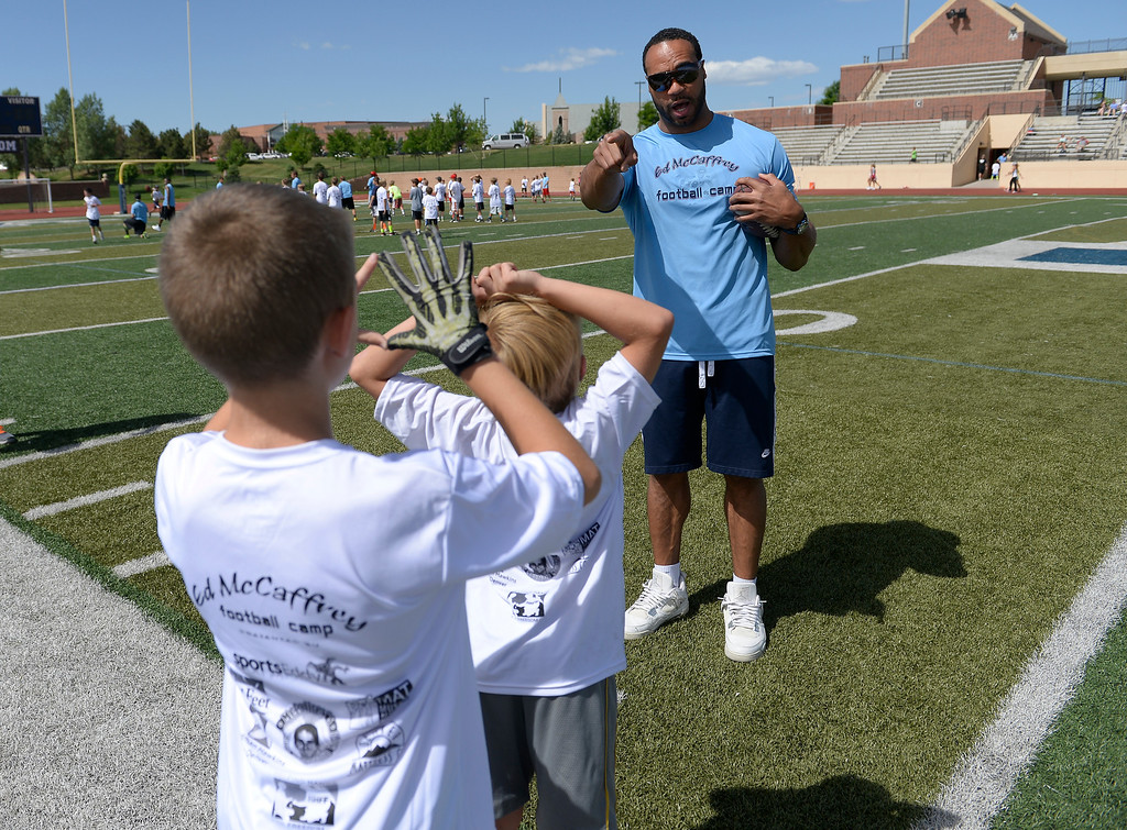 ". Former Broncos RB Kyle Johnson helps out during The Ed McCaffrey ""Open\"" Football Camp June 25, 2013 at Valor High School. Former Broncos star receiver Ed McCaffrey and other former pro football players conduct a football camp for kids ages 8-15 at Valor Christian High School.  (Photo By John Leyba/The Denver Post)"