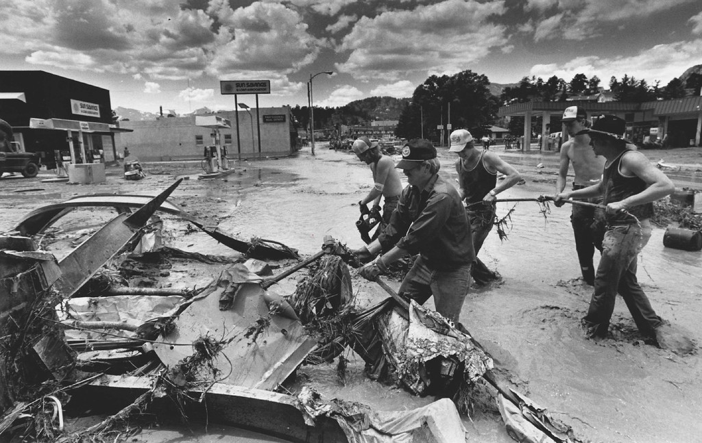 . 1983, FEB 15 - Estes Park Flood. Workers started clearing the mess before the waters had receded. The bill would allow persons damaged in the flood to go to court against the state to try to recover damages. (Duane Howell/The Denver Post)