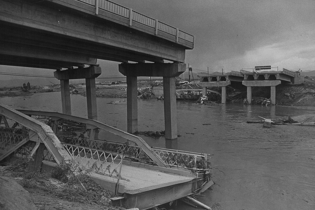 . JUN 18 1985  The New Spans on the W. Hampden Ave. Freeway Across the South Platte Are Gone. Trees, house trailers, lumber, sheds, oil drums and even cars piled up against the spans until each became a small dam. Finally the pressure proved too much, and the centers were swept away. In the Denver metropolitan area seven bridge* were washed out completely including the one in the photo. Another four or five will be closed until safety checks are made. Some of those may be closed permanently. Eleven others survived and were back in use, providing the limited traffic flow across- the city. Rail bridge* also were lost in the flood.  (Bill Johnson/ The Denver Post)