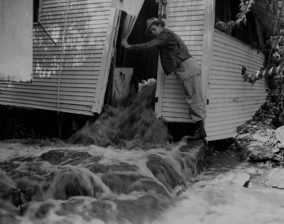 . MAY 12 1947 - Three feet of water cascades through a cottage in Manitou near where a flash flood Saturday took the life of a 14-year-old girl did thousands of dollars damage. Looking on is Deputy Dean K. Napier, Manitou. The lights were still burning in the damaged house. (Floyd H. McCall/ The Denver Post)
