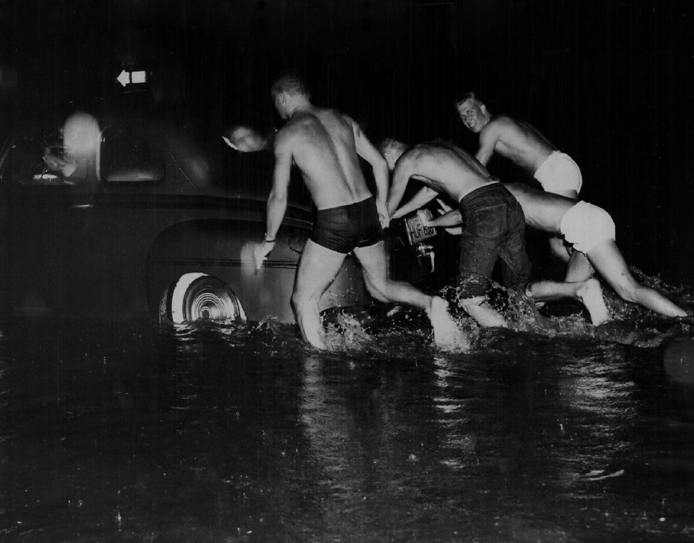 . 1957, AUG 17  Storm catches lowry airmen ready for action A3/C William O.Walls (left), 19, and his buddies were all prepared for the three feet of water in which their car stalled Saturday night at E. 14th Ave. and Jasmine St. The Lowry airmen were returning to the air base from El Dorado Springs where they had been swimming, and it was a simple matter for them to get back into their swimming trunks and push the car to higher ground. Seven autos were stalled by storm in this Denver area.   (Ed Maker/ The Denver Post)