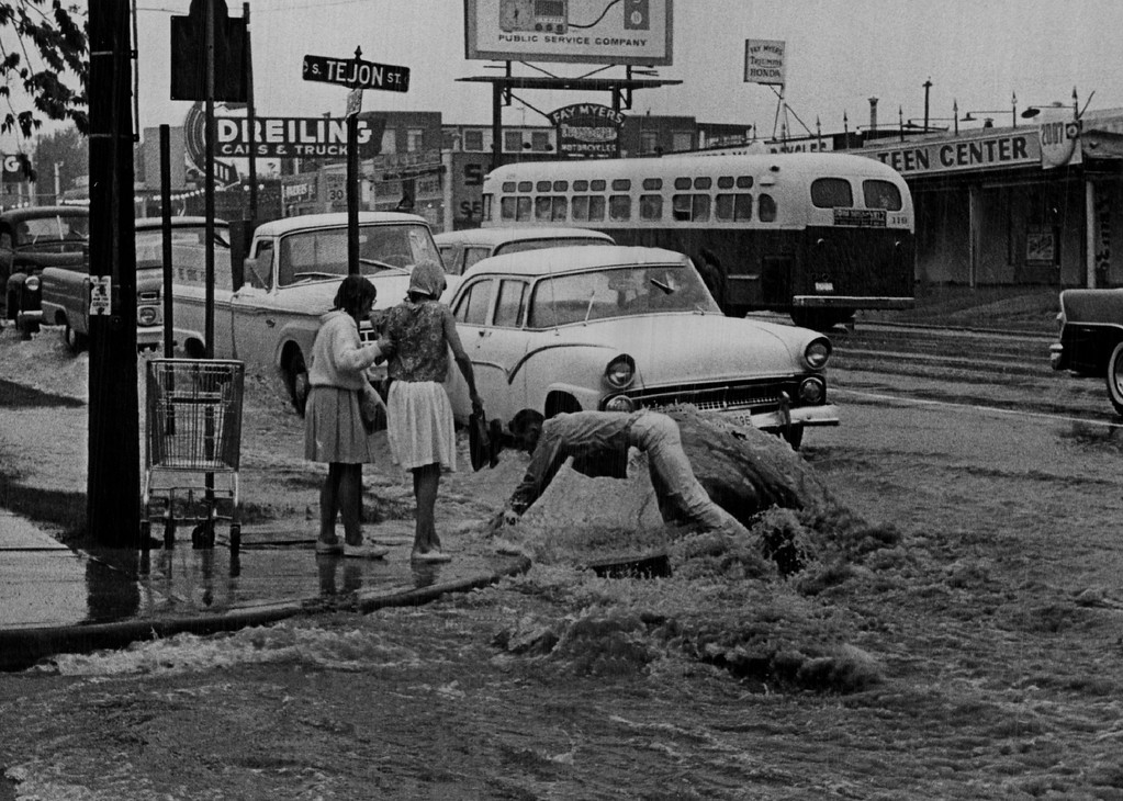 . JUN 5 1965 - Just before he reaches the corner, the  unidentified youth stumbles and tumbles forward for a though dunking. The girls watched the entire scene and were reassured in their decision not to try to cross the flooding Denver street. (Bill Johnson/ The Denver Post)