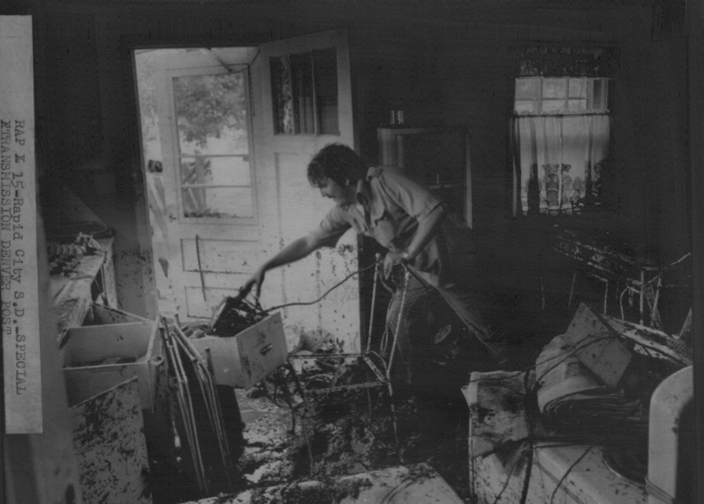 . JUN 11 1972  Steven Hughes Cleans out Debris of his kitchen after flood water hit the house and carried it into a row of trees. He said trees saved him, his wife, susan, and the house.  (David Cupp/The Denver Post)
