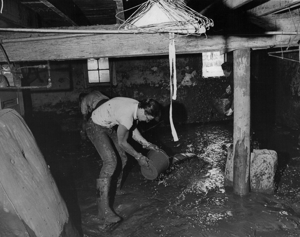. JUL 1 1965 - Gary Wormington scoops mud from basement of Corbone home. (Dave Buresh/ The Denver Post)