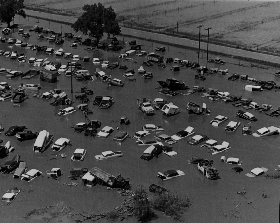 . 1965, JUN 18  A car lot is flooded southeast of Greeley near the point where the Cache La Poudre River flows in from the west and joins the South Platte River which then flows east. Car lot S. East of Greely  (Bill Johnson/ The Denver Post)