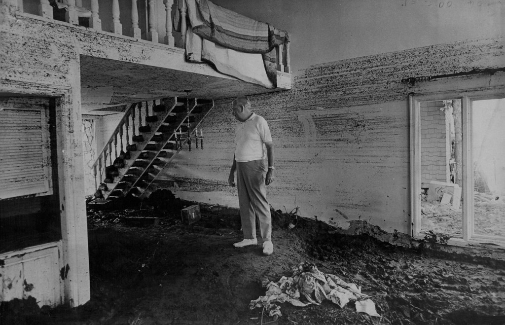 . JUN 13 1974 - Lloyd Atwater stands on carpet of mud that was deoposited when a wall of water smashed through his house in Dark Canyon area of Rapid Creek, Streaked lines on back wall indicate depth of flood. (Denver Post photo)