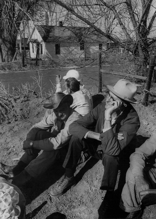 . APR 13 1973  Bill Tetiva, 64,-right, and John Romans, 72, sit on high ground south of Ker­sey speculating on their homes while floodwaters swept through the town.  (Dave Buresh/ The Denver Post)