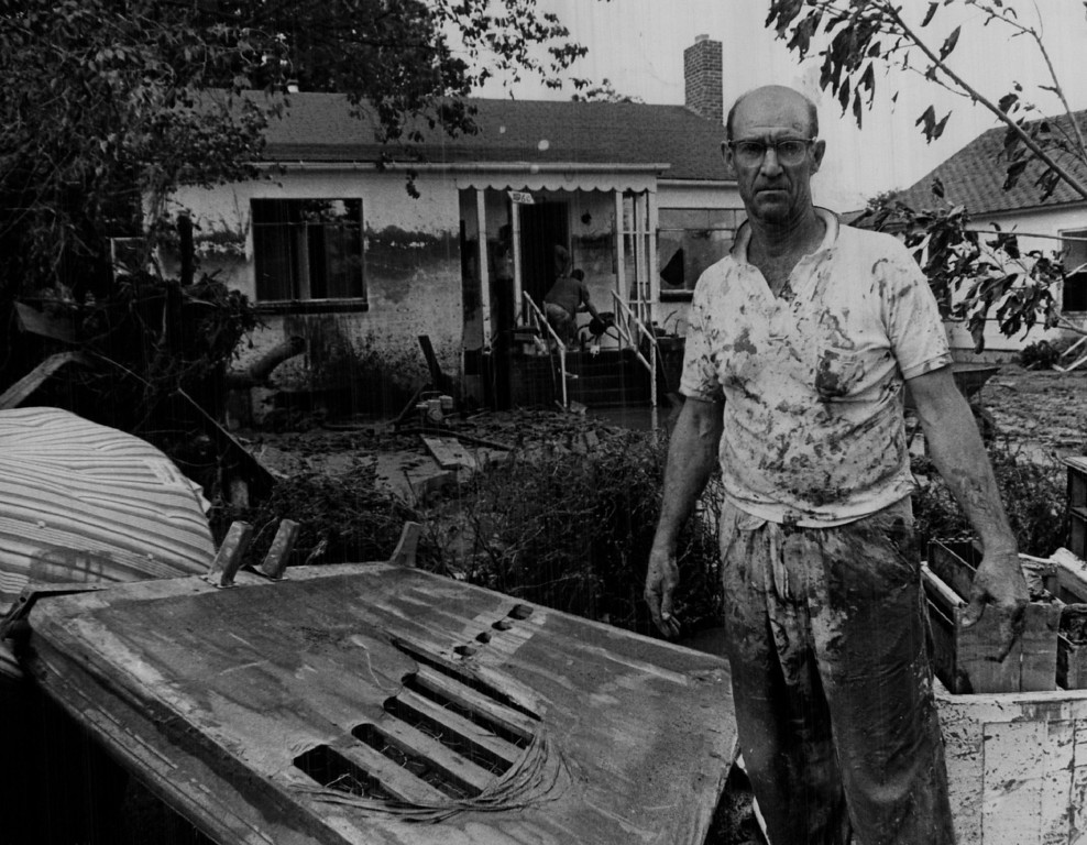 . JUL 15 1965  William H.Haines, splattered with mud, is shown at his flood-damaged home at 1960 S. Huron St. in Denver as he and friends began the massive cleanup.  (Duane Howell/ The Denver Post)