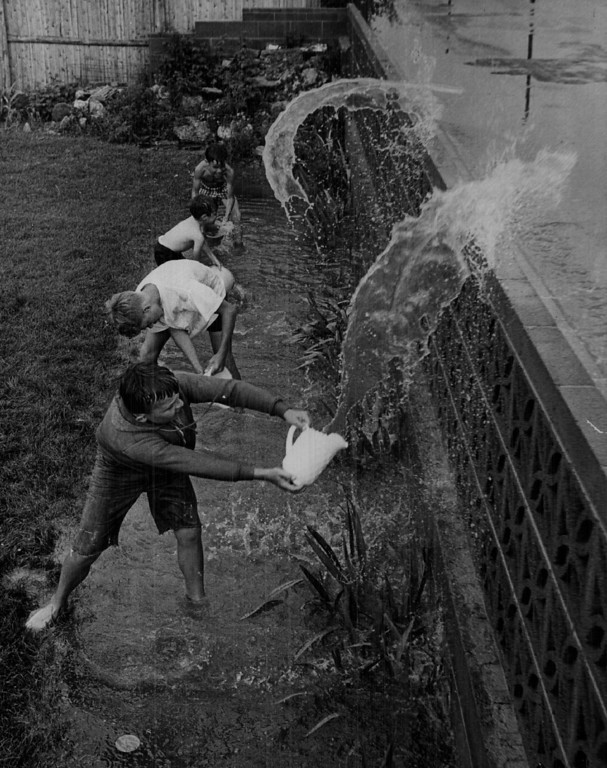 ". JUL 14 1967 - Adams county youngsters enjoy their ""work. \"" Not long before this photo was taken, water stood 18 inches deep in back yard of Herbert Klein, 7204 Santa Fe Drive. Trying to hasten runoff by throwing water into street are, from top, Mark Zimmer, Kevin Klein, Herbert Klein, Keith Howitt. (Bill Peters/ The Denver Post)  Top to bottom  Mark Zimmer, 8, 7205 Inca St.  Kevin Klein, 5, of 7204 Santa Fe. Drive. John Praml, 14, of 7214 Santa Fe. Drive. Keith Howitt, 13, of 7213 Santa Fe Drive. 7204 Santa Fe Drive home of Herbert Klein"