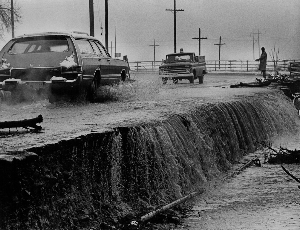 . APR 26 1971  Coal Creek Spills out of its banks and Across road Monday near the boulder turnpike and Dillon Road. Joe Udovich, Boulder County worker, directs traffic after downpour which left gutters gushing and swelled some creeks and streams out of the banks.   (Duane Howell/ The Denver Post)
