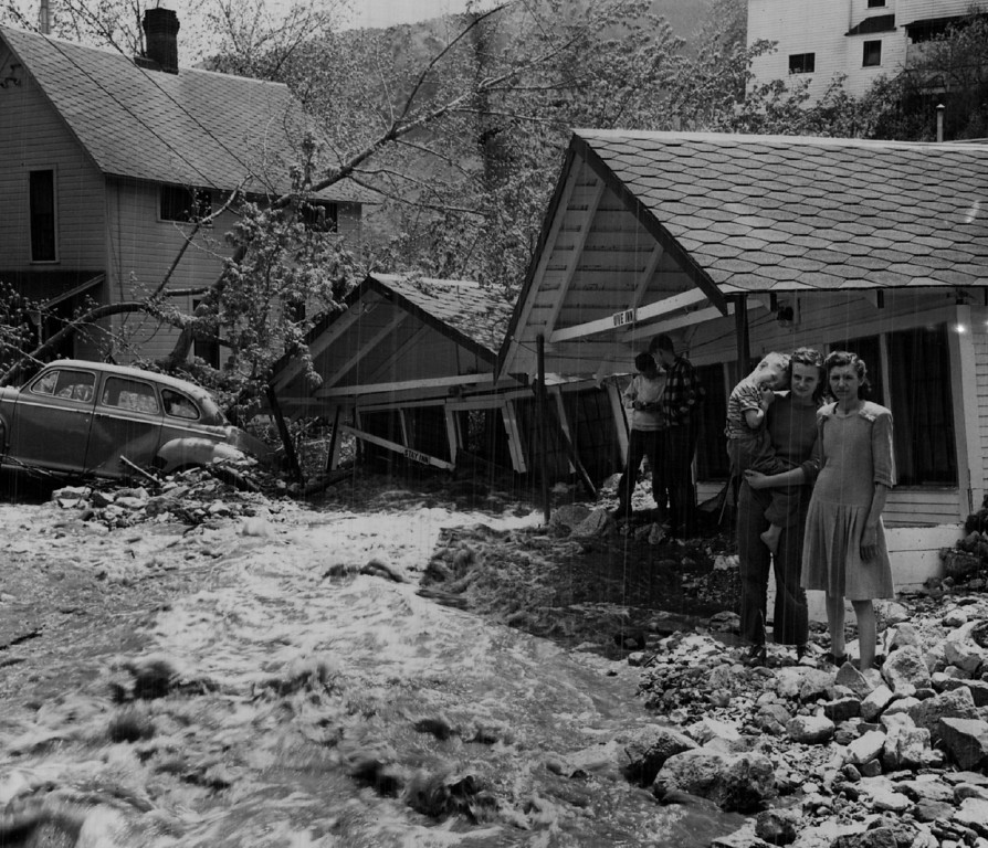 . MAY 12 1947  A Narrow Escape from the roaring flood waters is recalled by Mrs. C.N.Shaull (at right) of Manitou, as she stands in front of her cottage with her daughter, Katherine, 16, and son Fred, 6. They got out of their home at 7:15 p.m. Saturday just ahead of the flash flood.   (Floyd H. McCall/ The Denver Post)