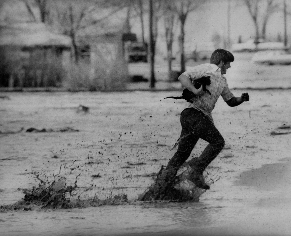 . APR 13 1973 - William Shamray, Kersey, Colo., Races through Floodwaters with a cat he rescued from a roof. The northern two-thirds of the community received the brunt of the flood with areas in the extreme south end escaping completely. (Dave Buresh/ The Denver Post)