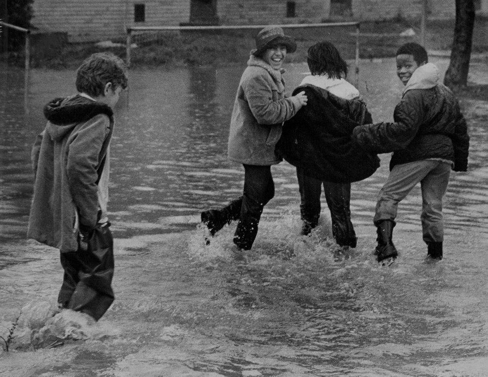 . MAY 2 1973  The high water from rain washing into low spots was a lark for these boys who live in Stapleton Homes, a Den­ver Housing Authority complex at.51st Ave. and Broad­way. Water collected in the low northwest corner of the project, licking at the doorsteps of a few apartment complexes. The project wasn\'t evacuated by police, but officers advised those persons in water-surrounded build­ings to stay on upper floors. Disaster officials  area estimated that several thousand persons were forced to leave their homes because of the Sunday flooding.  (John Beard/ The Denver Post)