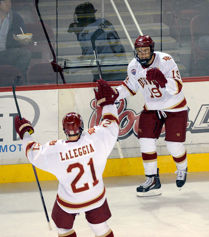 . Denver Pioneers Daniel Doremus (19) celebrates his short handed goal with Pioneers Joey Laleggia (21) on a back hand shot over University of New Brunswick G Charles Lavigne (31) during the second period October 6, 2013 at Magness Arena. (Photo by John Leyba/The Denver Post)