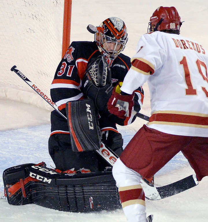 . University of New Brunswick G Charles Lavigne (31) makes a save as Denver Pioneers Daniel Doremus (19) looks on during the first period October 6, 2013 at Magness Arena. (Photo by John Leyba/The Denver Post)