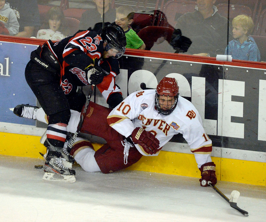 . Denver Pioneers David Makowski (10) gets pounded along the boards by University of New Brunswick Cam Crithlow (23) during the first period October 6, 2013 at Magness Arena. (Photo by John Leyba/The Denver Post)