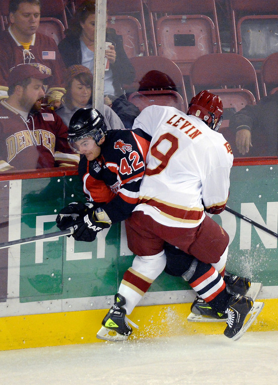 . Denver Pioneers Gabe Levine (9) pounds University of New Brunswick Ben Shutron (42) in to the boards during the first period October 6, 2013 at Magness Arena. (Photo by John Leyba/The Denver Post)