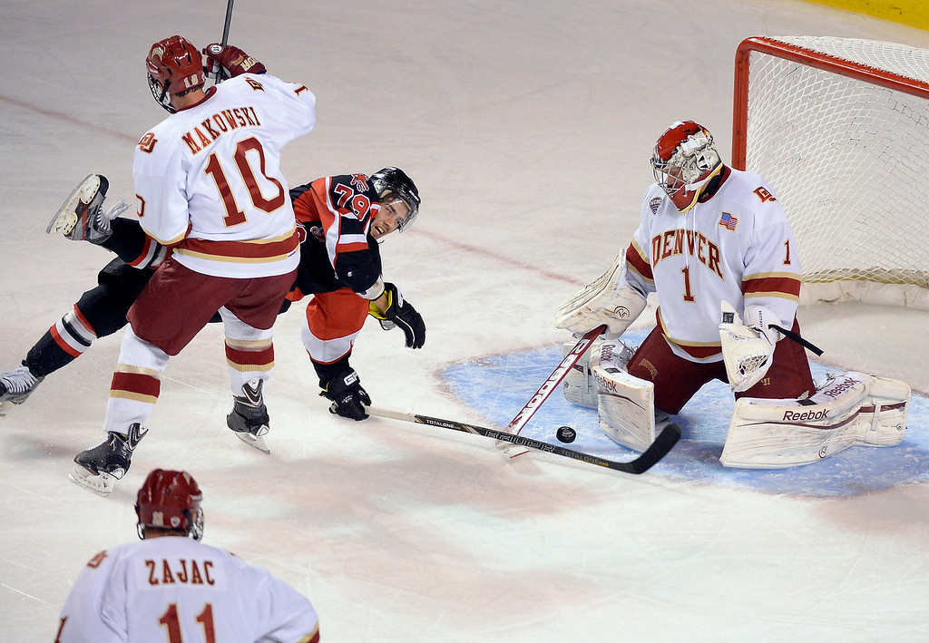 . Denver Pioneers David Makowski (10) hits University of New Brunswick Thomas Nesbitt (79) off the puck as Pioneers G Sam Brittain (1) makes the save during the first period October 6, 2013 at Magness Arena. (Photo by John Leyba/The Denver Post)