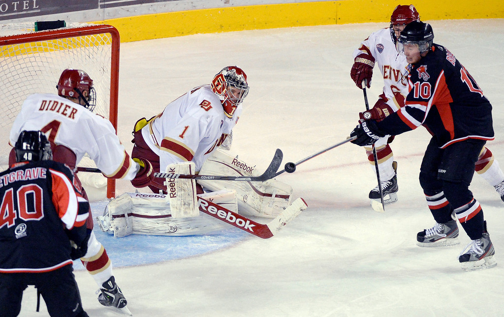 . Denver Pioneers G Sam Brittain (1) makes a save as the puck sails up with Denver Pioneers Josiah Didier (4) and University of New Brunswick Cam Braes (10) poking at it in front of the goal during the second period October 6, 2013 at Magness Arena. (Photo by John Leyba/The Denver Post)