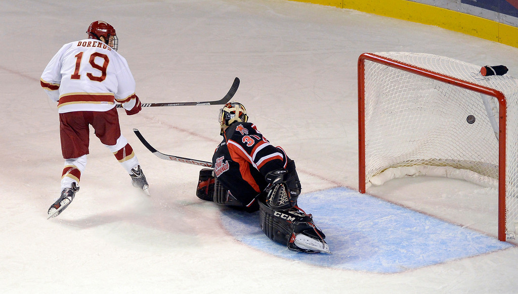 . Denver Pioneers Daniel Doremus (19) scores a short handed goal on a back hand shot over University of New Brunswick G Charles Lavigne (31) during the second period October 6, 2013 at Magness Arena. (Photo by John Leyba/The Denver Post)