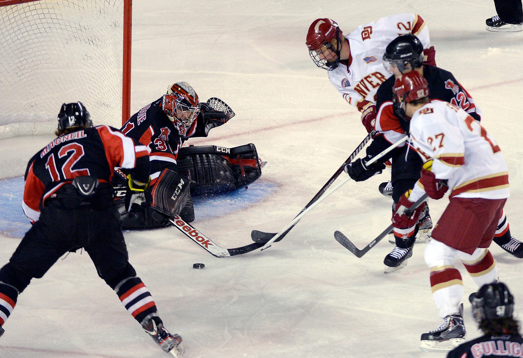. University of New Brunswick G Charles Lavigne (31) pokes the puck away with his stick as Ty Loney (12) tries to get to it during the first period October 6, 2013 at Magness Arena. (Photo by John Leyba/The Denver Post)