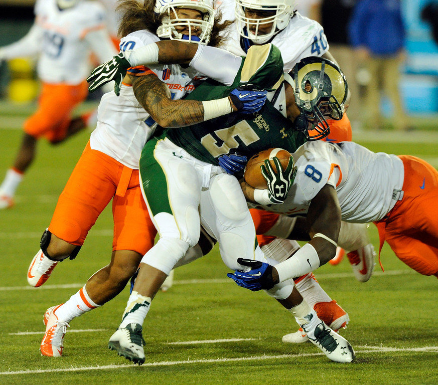 . FORT COLLINS, CO. - NOVEMBER 2: CSU running back Kapri Bibbs (5) was brought down by Broncos safety Jeremy Ioane (10 and defensive end Demarcus Lawrence (8) in the first quarter. The Colorado State University football team hosted Boise State Saturday night, November 2, 2013. Photo By Karl Gehring/The Denver Post