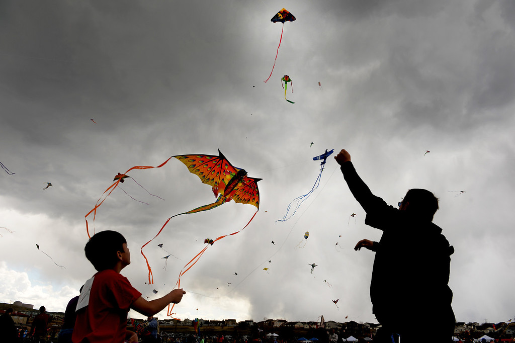 . Carlos Vallejos, 8, left and his cousin Chris Beam, right, of Denver, Vasalisa  try to get Vallejos\'  dragon kite in the air during the 12th annual Arvada Kite Festival held at the Stenger soccer complex in Arvada, Colorado, on April 6, 2014.  Hundreds of people braved cold temperatures , some rain and gusty winds to fly their kites  of all different sizes, shapes, and colors. Activities included kite making classes and competitions for highest kite, smallest kite, largest kite and most visually appealing kite.  (Photo By Helen H. Richardson/ The Denver Post)