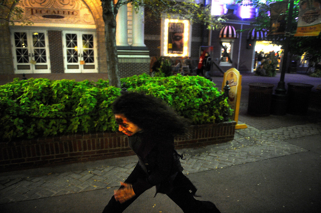 . Zombie Cara Fresquez runs down the walkway at Elitch Gardens as she chases visitors to Fright Fest 2013.  (Photo By Erin Hull/The Denver Post)