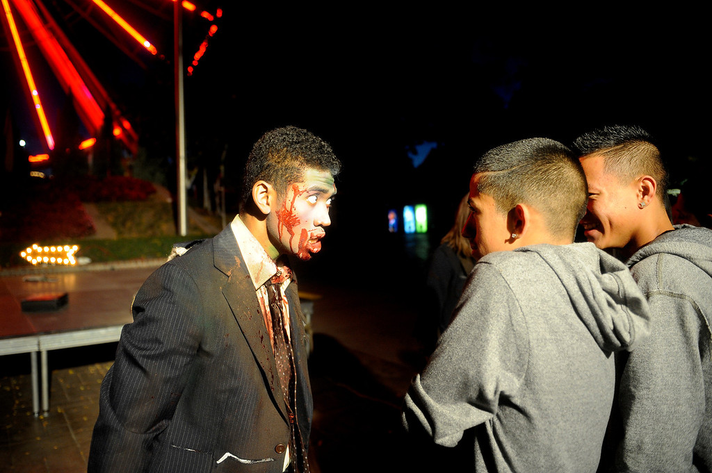 . Zombie Sergio King stares down Manuel Sosa and Johnny Sysavat. King was performing during The Awakening, a zombie show at Fright Fest 2013 at Elitch Gardens.   (Photo By Erin Hull/The Denver Post)