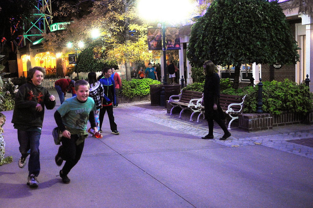 . People scream and run as they are scared by a zombie wandering the streets at Fright Fest 2013 at Elitch Gardens in Denver on Oct. 11, 2013.   (Photo By Erin Hull/The Denver Post)