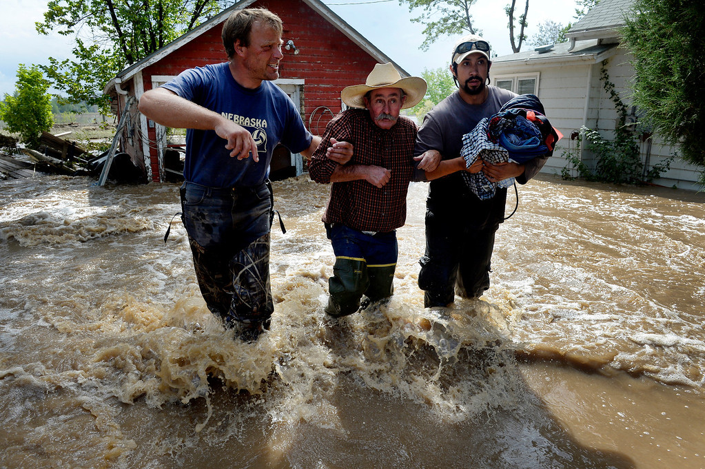 . Dan Hull, center, is assisted by Brian Marquardt, left, and Scott Johnson after rescuing Hull\'s two cats and gathering some items from his flooded home on Hygiene Road in Hygiene, Colorado on September 14, 2013.  (Photo By Craig F. Walker/The Denver Post)