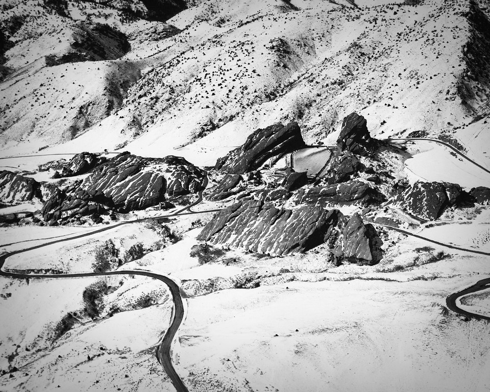 . FEB 23 1953. The Red Rocks amphitheater � a colorful, popular foothills site enjoyed by thousands during spring, summer and fall�stands cold and deserted in this aerial photo. Main access roads (left and right) frame the amphitheater and parking areas in this wintry view, made looking southwest. (Dean Conger/The Denver Post)