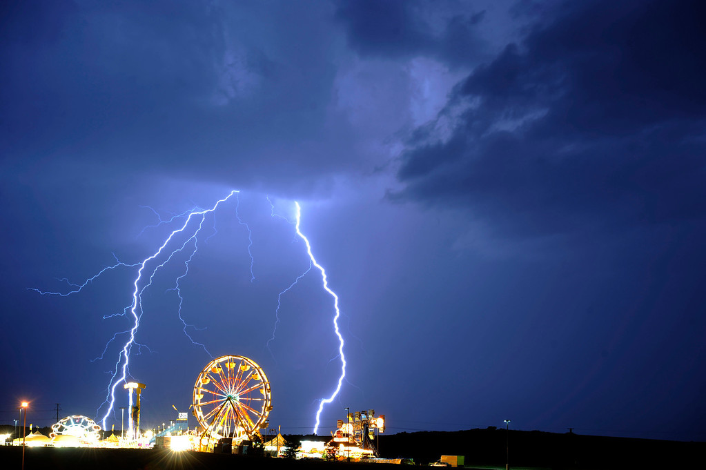 . Lightning strikes over the Mountain Vista Carnival as another round of rain and lightning lights up the western skies on July 13, 201 in Highlands Ranch.  (Photo by John Leyba, The Denver Post)