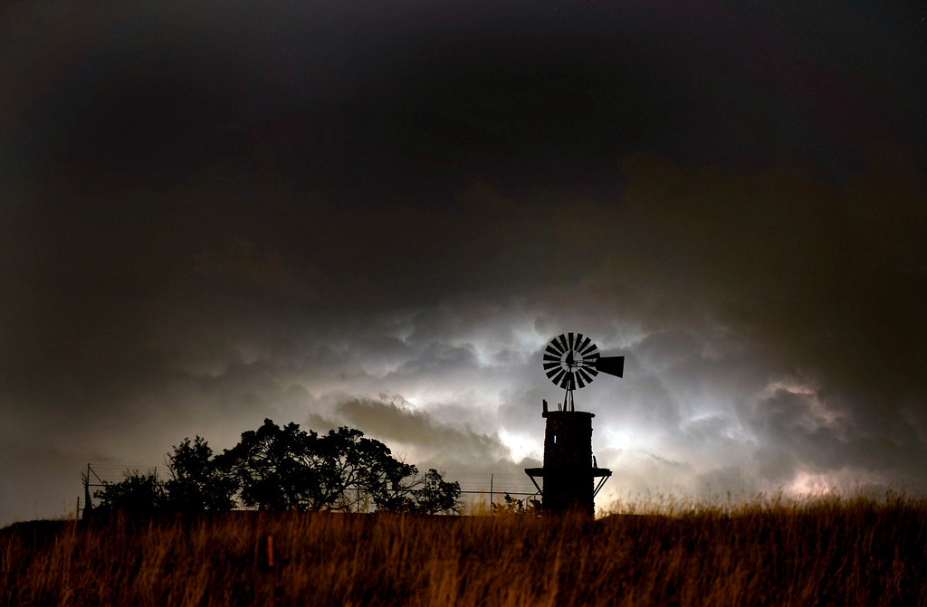 . A historic windmill in Highlands Ranch is silhouetted by lightning and billowing clouds to the south. The photo was taken on Tuesday morning at 1:17 a.m. Windmills, like the one pictured, were very important to ranchers in Highlands Ranch because they helped supply water to cattle in various pastures. The historic windmill stands today on the ranch property. (Photo by John Leyba/The Denver Post)