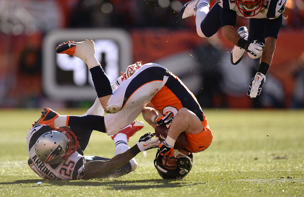. DENVER, CO - JANUARY 19: Denver Broncos wide receiver Wes Welker (83) makes a catch in the second quarter and is tackled by New England Patriots cornerback Kyle Arrington (25). The Denver Broncos take on the New England Patriots in the AFC Championship game at Sports Authority Field at Mile High in Denver on January 19, 2014. (Photo by Hyoung Chang/The Denver Post)