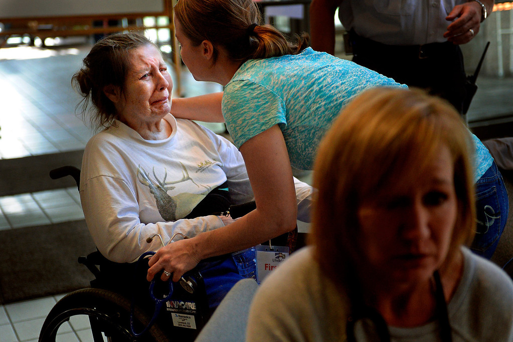 . Susan Elston, overwhelmed after being rescued from the flooded town of Lyons, receives help from a first-aid station at LifeBridge Christian Church in Longmont on Sept. 13, 2013.