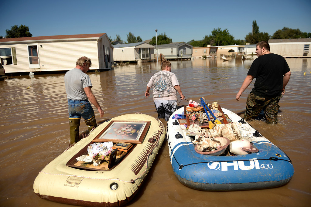 . EVANS, CO - SEPTEMBER 17: From left, Dale Reeves, Kathryn Reeves, and Trent Mayes helps their  elderly family member in Evans carry out belongings from their flooded homes, September 17, 2013. Massive flooding continues to hit Colorado. (Photo By RJ Sangosti/The Denver Post)