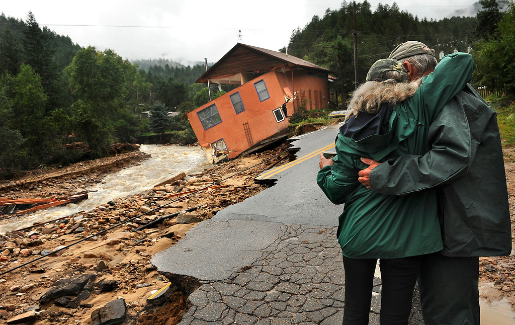 . Residents embrace near a washed-out home in Jamestown, Colo. on Sept. 14, 2013. Flooding hit the mountain community extremely hard, and residents have been trapped for three days with no road into or out of town.