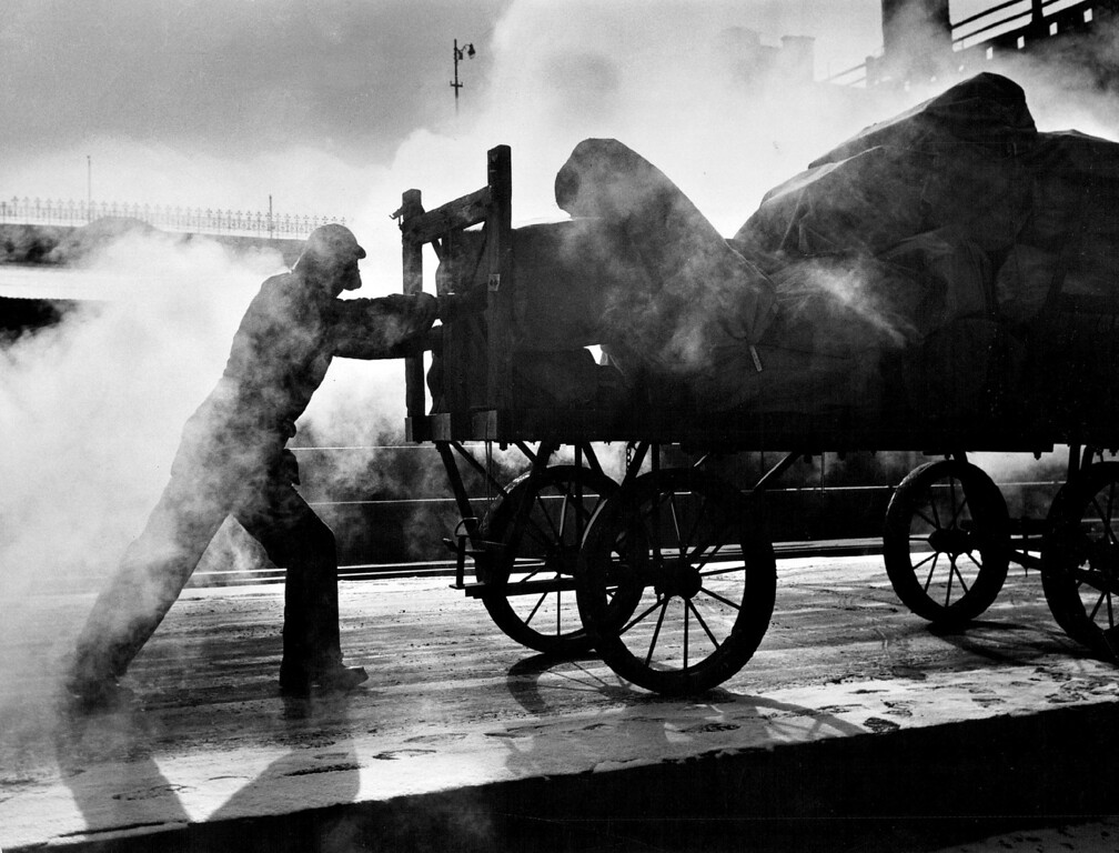 . A chill mist envelops Nick DeBaca as he pushes a baggage cart along the dock at Denver\'s Union Station Wednesday morning with temperatures hovering near the zero mark. Mercury dropped to 1-above early Wednesday, with a high of only 15 expected for days in January of 1957.  (Photo by David Mathias/The Denver Post)